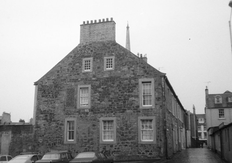View of gable end of 20-22 Academy Street facing Fort Street, with top of Town Hall Steeple showing above roof line.