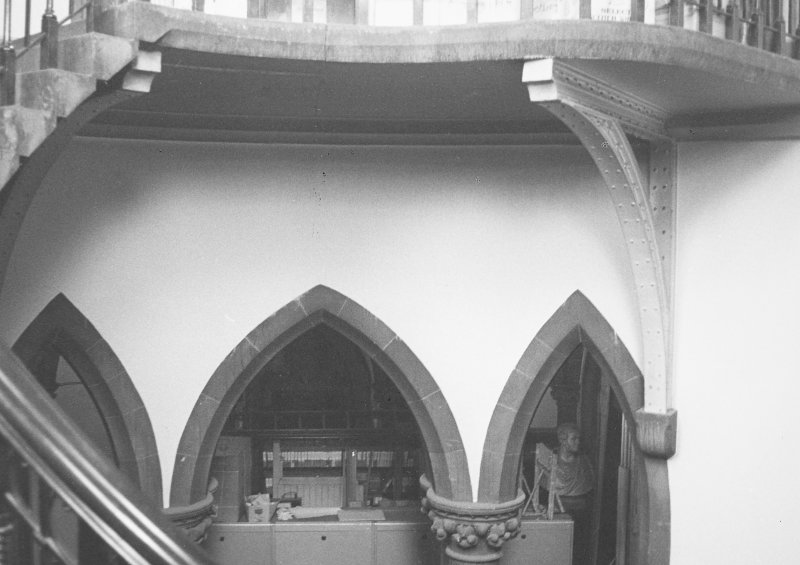 Interior view of staircase and arcading.