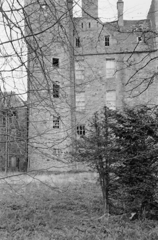 View of Aboyne Castle in a derelict state through trees.