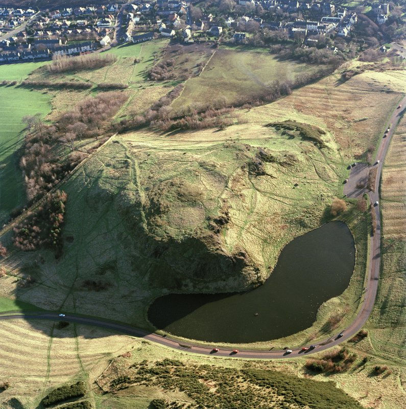 Oblique aerial view of Holyrood Park centred on the remains of a fort, field bank and scooped settlement, taken from the NNW.