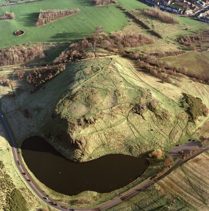 Oblique aerial view of Holyrood Park centred on the remains of a fort, field bank and scooped settlement, taken from the W.