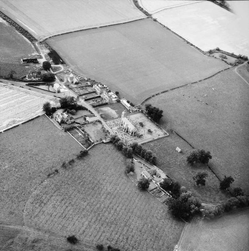Oblique aerial view centred on church from SE.