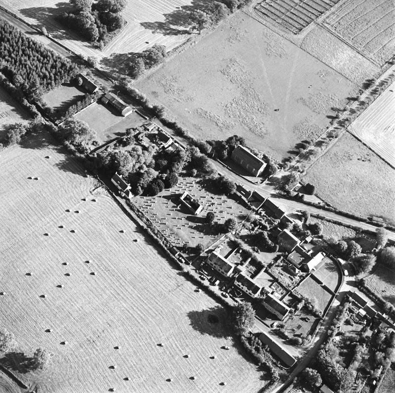 Oblique aerial view centred on the remains of the church and burial ground with old church and hotel adjacent, taken from the NW.