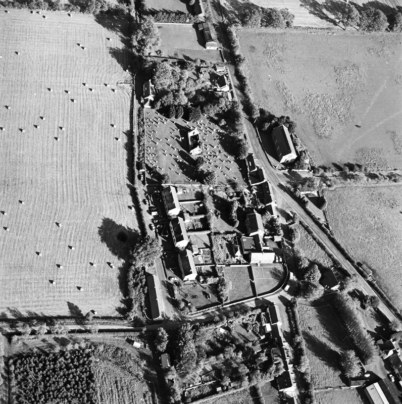 Oblique aerial view centred on the remains of the church and burial ground with old church and hotel adjacent, taken from the W.
