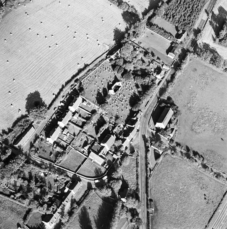 Oblique aerial view centred on the remains of the church and burial ground with old church and hotel adjacent, taken from the SW.