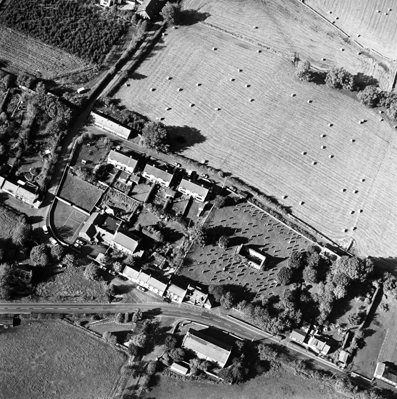 Oblique aerial view centred on the remains of the church and burial ground with old church and hotel adjacent, taken from the SE.