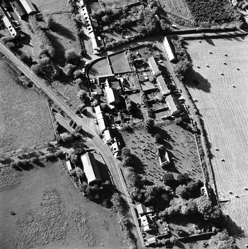 Oblique aerial view centred on the remains of the church and burial ground with old church and hotel adjacent, taken from the E.