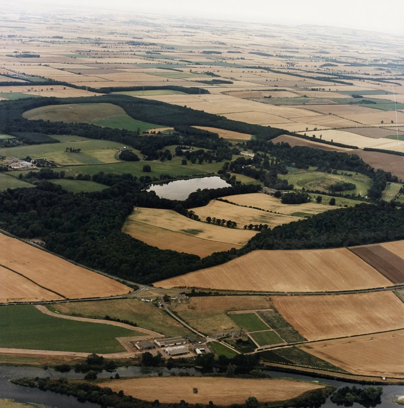 General oblique aerial view centred on the country house, stable, laundry, offices, museum and lake, taken from the SW.