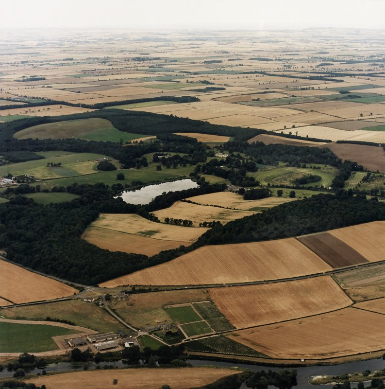 General oblique aerial view centred on the country house, stable, laundry, offices, museum and lake, taken from the SSW.