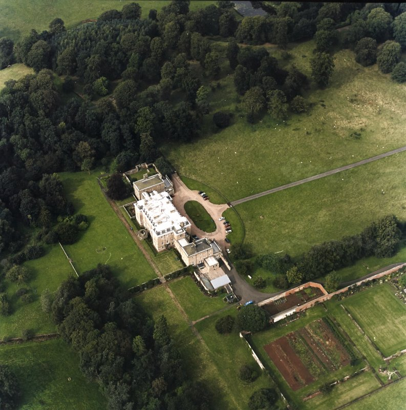 Oblique aerial view centred on the country house with walled garden adjacent, taken from the SSE.