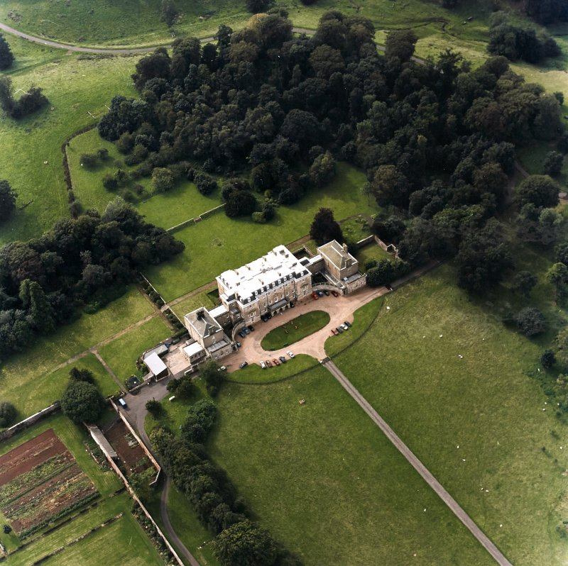 Oblique aerial view centred on the country house with walled garden adjacent, taken from the E.