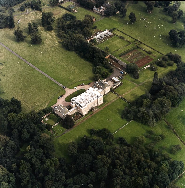 Oblique aerial view centred on the country house with walled garden adjacent, taken from the W.