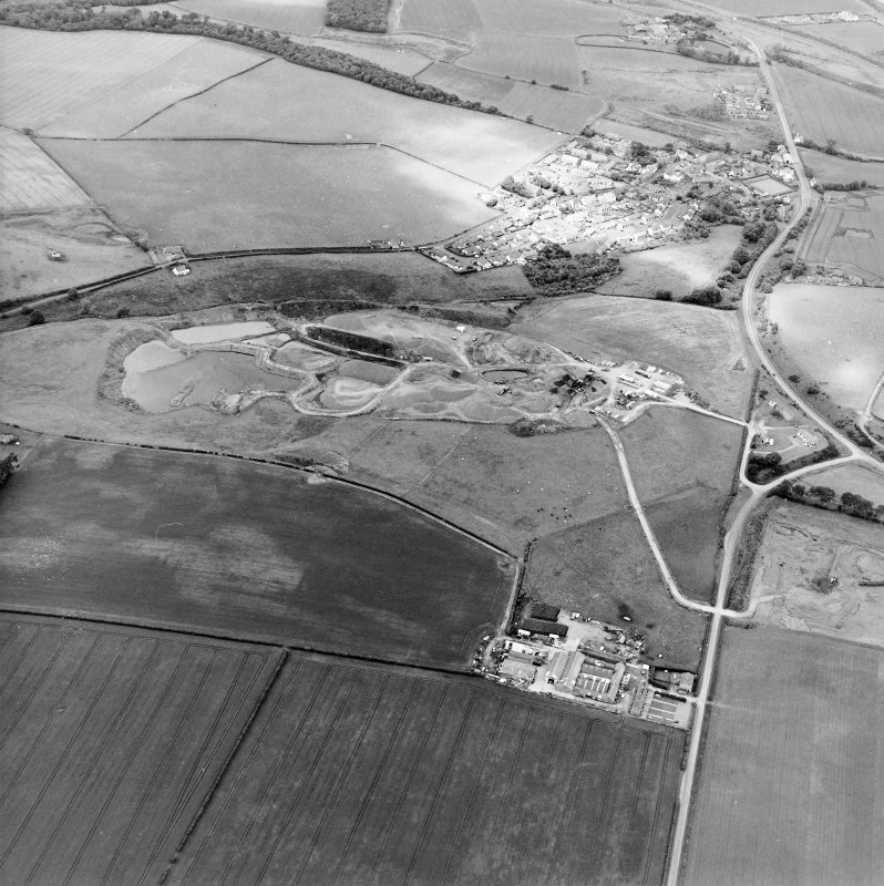 Oblique aerial view centred on the quarry with the village adjacent, taken from the S.