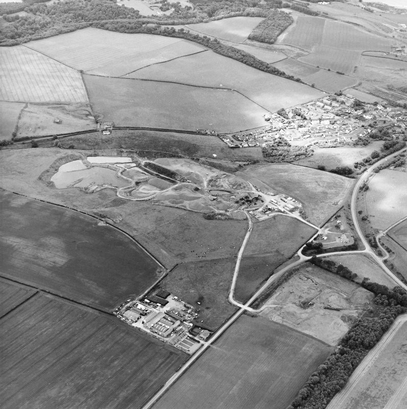 Oblique aerial view centred on the quarry with the village adjacent, taken from the SSE.