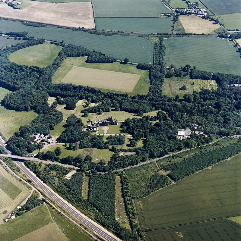 Oblique aerial view centred on the country house, with the farmsteading and the gate-lodge adjacent, taken from the NNW.