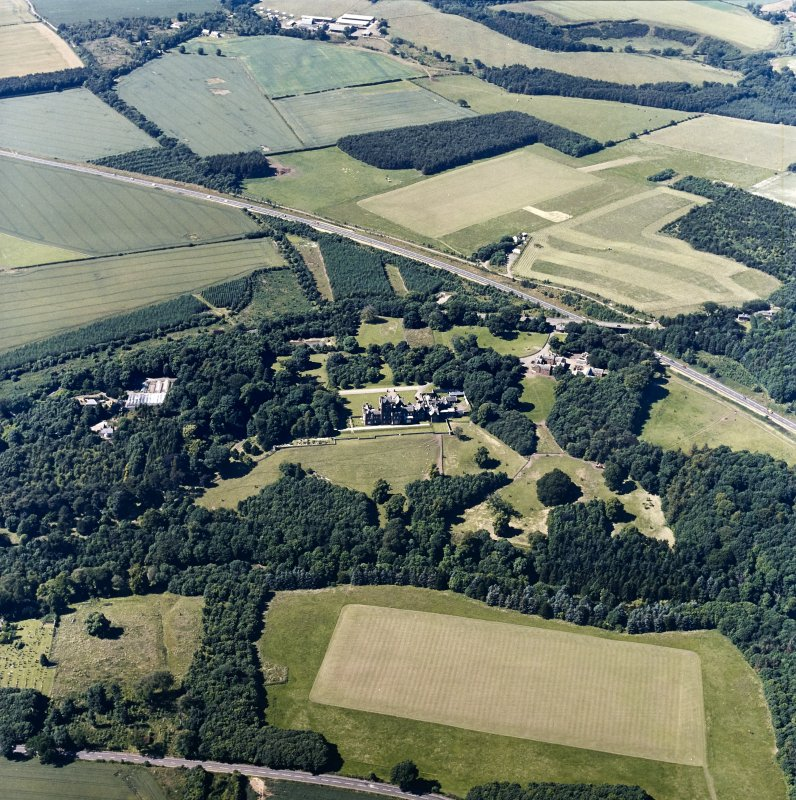 Oblique aerial view centred on the country house, with the farmsteading and the gate-lodge adjacent, taken from the SE.