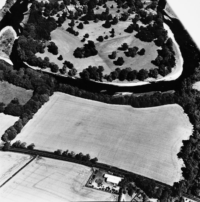 Oblique aerial view from SSW, centred on the cropmarks of a rectilinear settlement, and with Dryburgh Abbey, a dovecot and a country house visible in the upper half of the photograph.