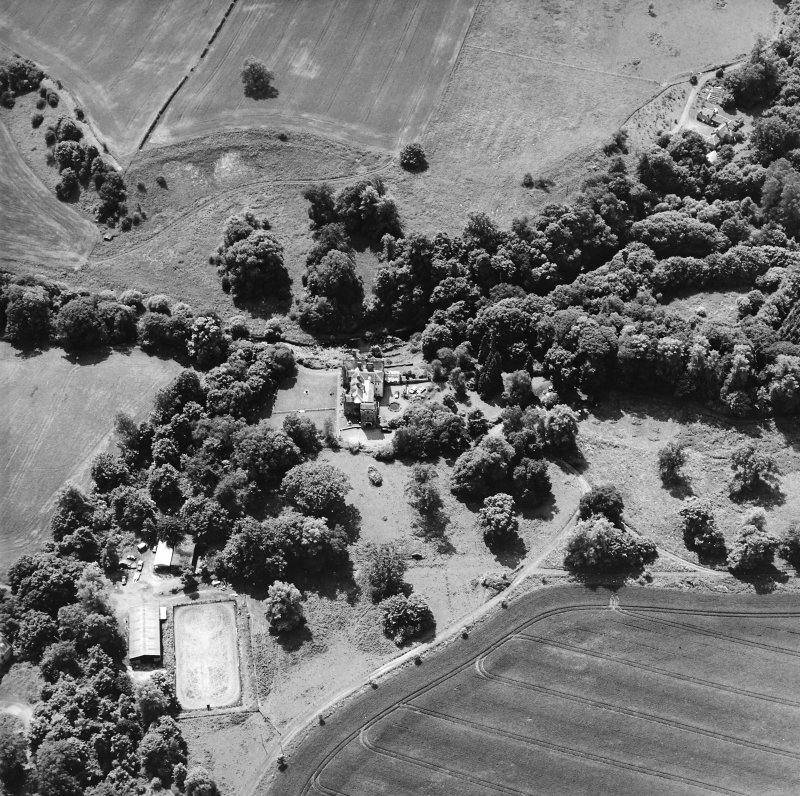 Oblique aerial view centred on the castle, tower-house and country house with the tower and walled garden adjacent, taken from the NE.
