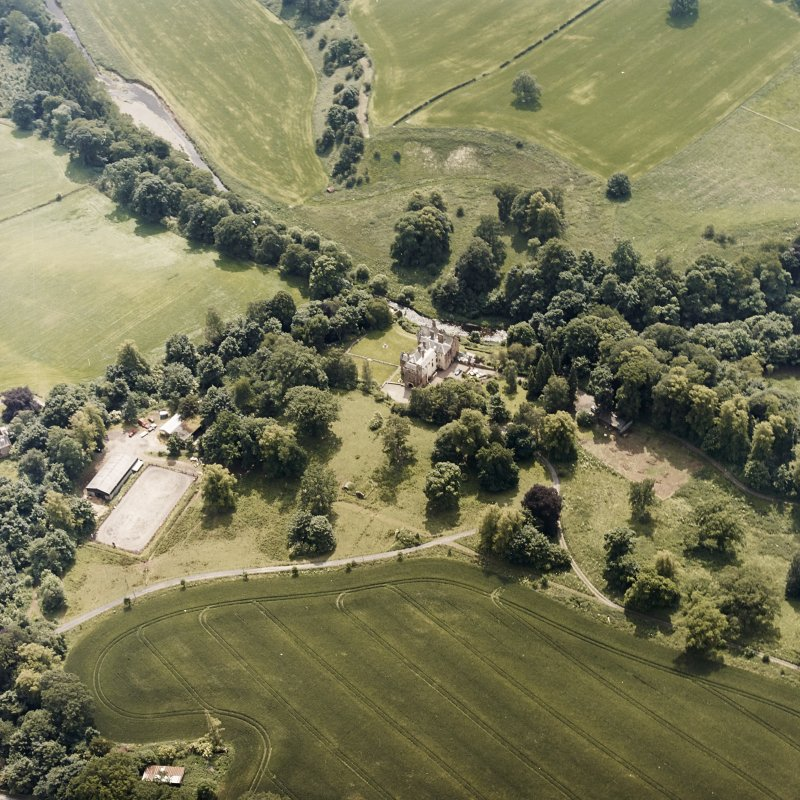 Oblique aerial view centred on the castle, tower-house and country house with the tower and walled garden adjacent, taken from the NNE.
