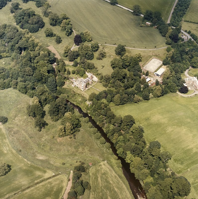 Oblique aerial view centred on the castle, tower-house and country house with the stables, tower and walled garden adjacent, taken from the S.