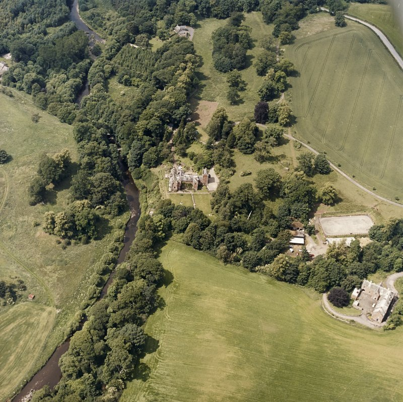Oblique aerial view centred on the castle, tower-house and country house with the stables, tower and walled garden adjacent, taken from the SE.