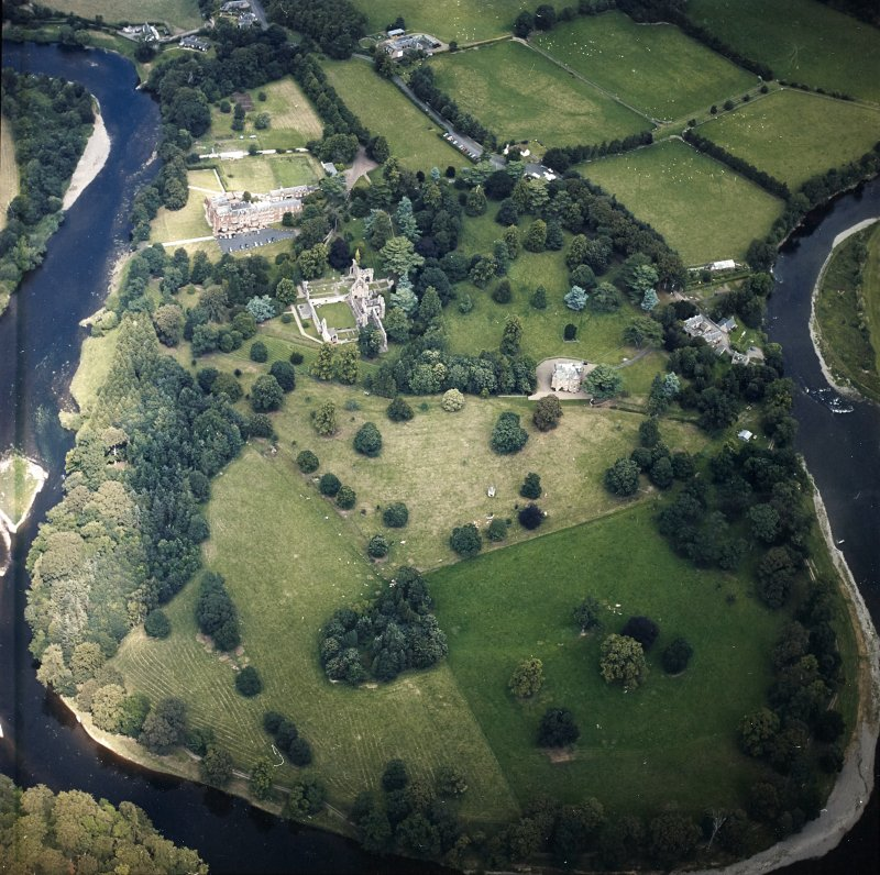 Oblique aerial view centred on the remains of the abbey, the country house and dovecot with the hotel and stables adjacent, taken from the SSW.