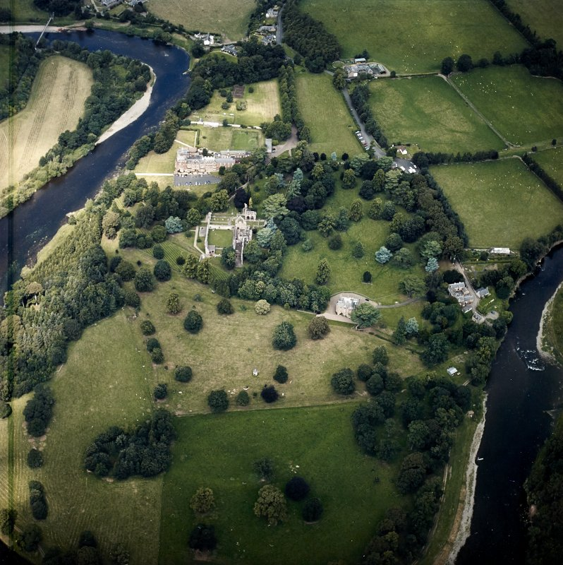 Oblique aerial view centred on the remains of the abbey, the country house and dovecot with the hotel and stables adjacent, taken from the S.