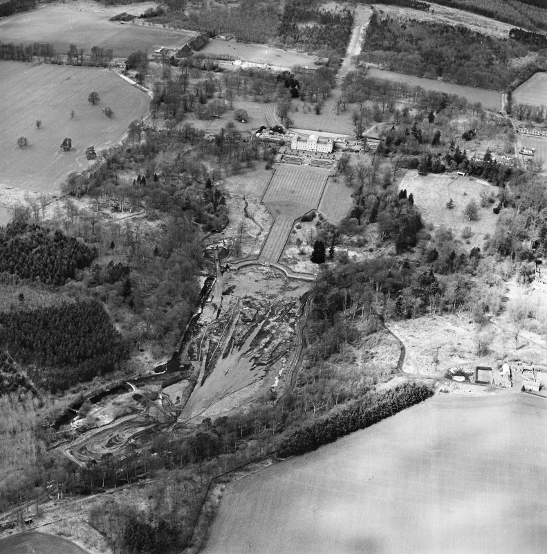 Oblique aerial view centred on the drained formal pond within Mellerstain House garden with country house and stables adjacent, taken from the ESE.