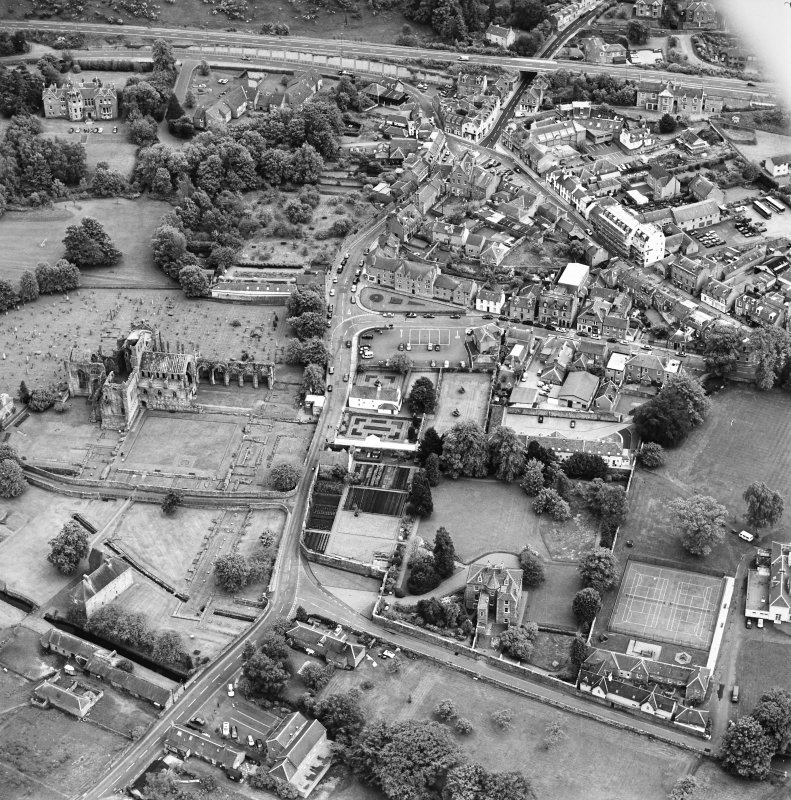Oblique aerial view of Melrose centred on Harmony house and the remains of the abbey, taken from the N.