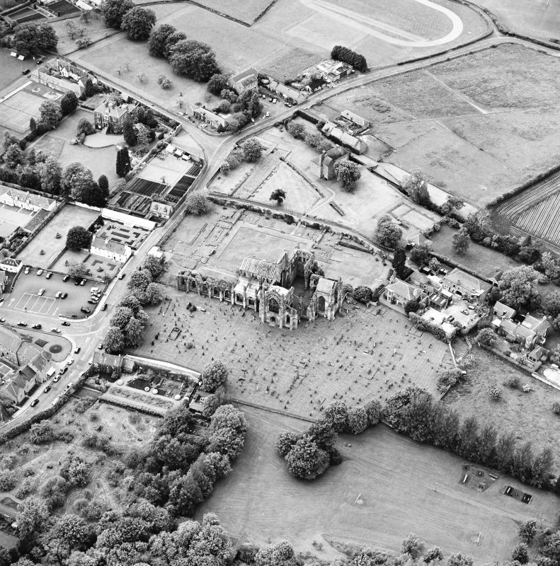General oblique aerial view of Melrose centred on Harmony house and the remains of the abbey, taken from the SE.