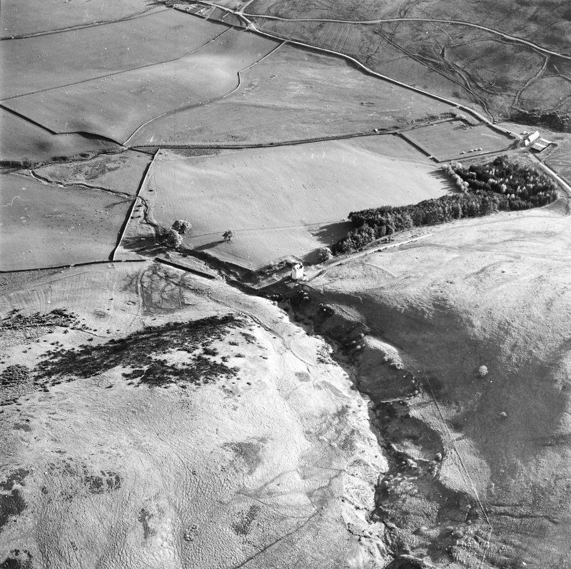 Oblique aerial view centred on the remains of the tower with the field system and tower adjacent, taken from the NE.