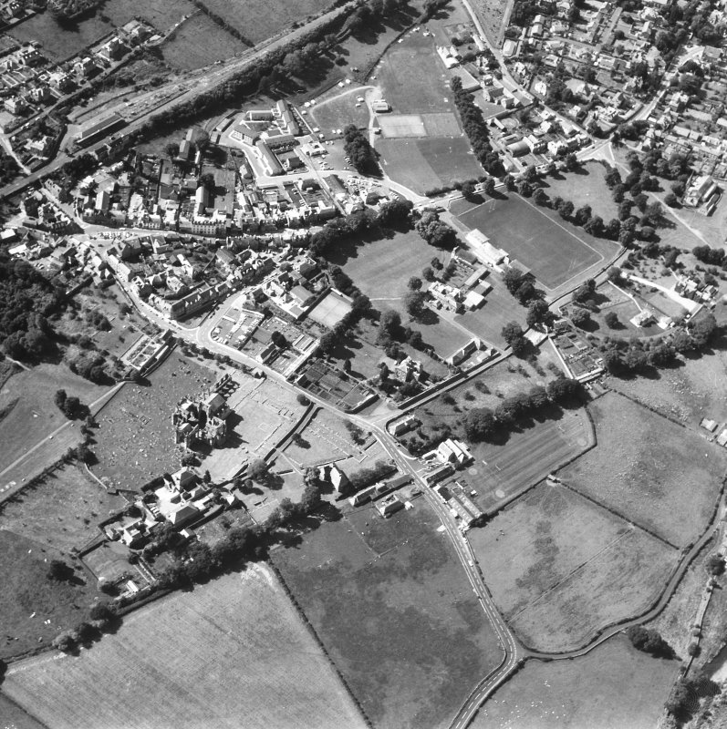 Oblique aerial view centred on abbey from NE.