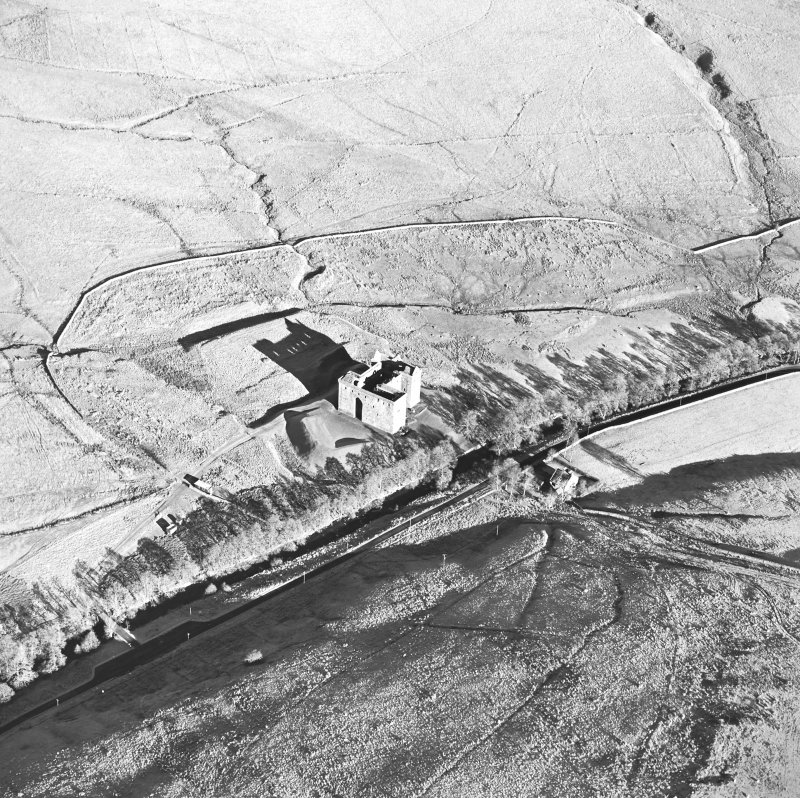 Oblique aerial view of Hermitage Castle centred on the remains of a castle, taken from the SW.