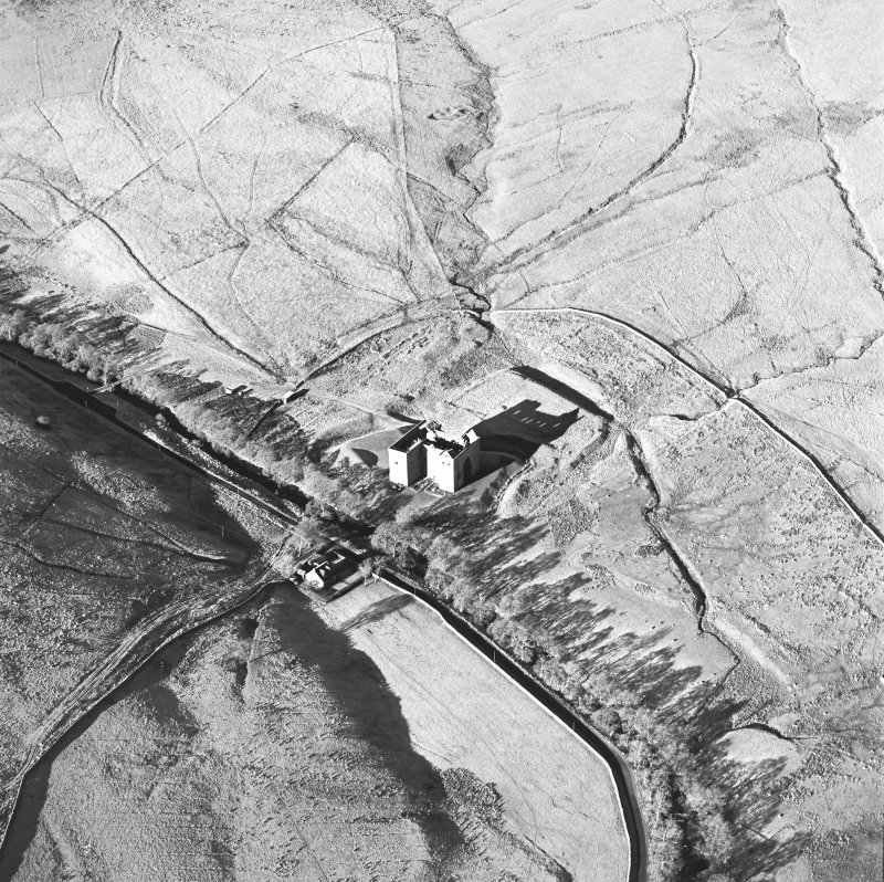 Oblique aerial view of Hermitage Castle centred on the remains of a castle, taken from the SE.