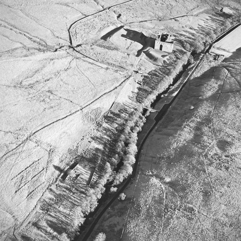 Oblique aerial view of Hermitage Castle centred on the remains of a castle with a chapel, boundary dyke and moated site adjacent, taken from the SW.