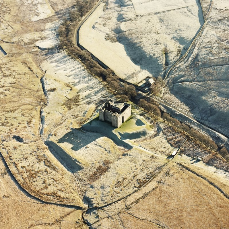 Oblique aerial view of Hermitage Castle centred on the remains of a castle and earthwork castle, taken from the NW.