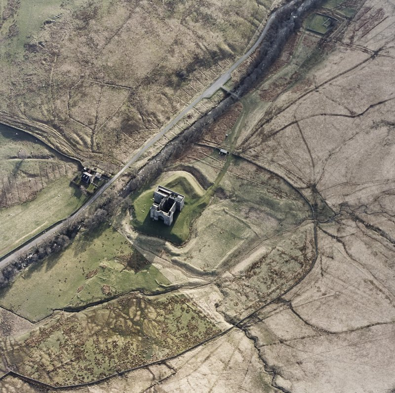 Oblique aerial view centred on the remains of the castle with chapel and moated site adjacent, taken from the NE.