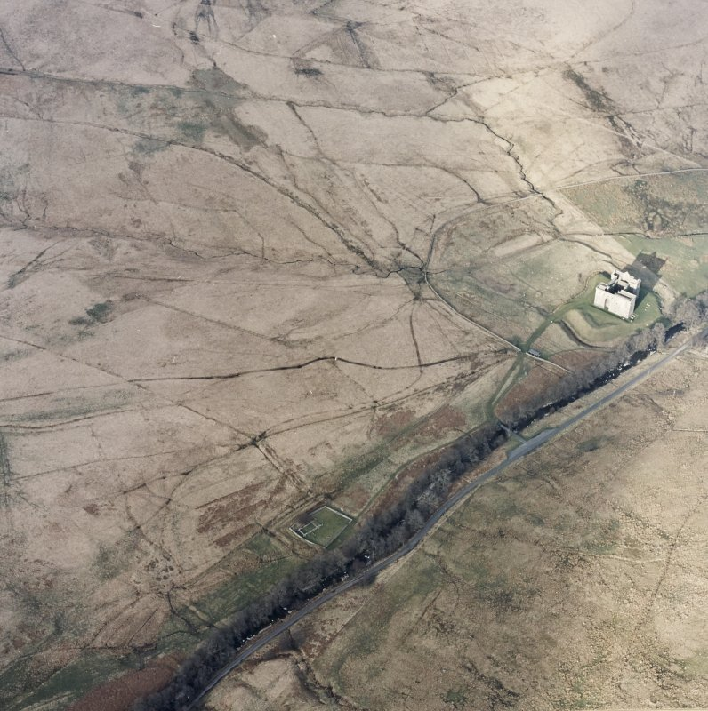 Oblique aerial view centred on the remains of the castle, chapel and moated site, taken from the SW.