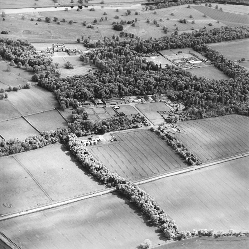 Oblique aerial view centred on the farmsteading, kennels and cottage with country house and formal garden adjacent, taken from the NNW
