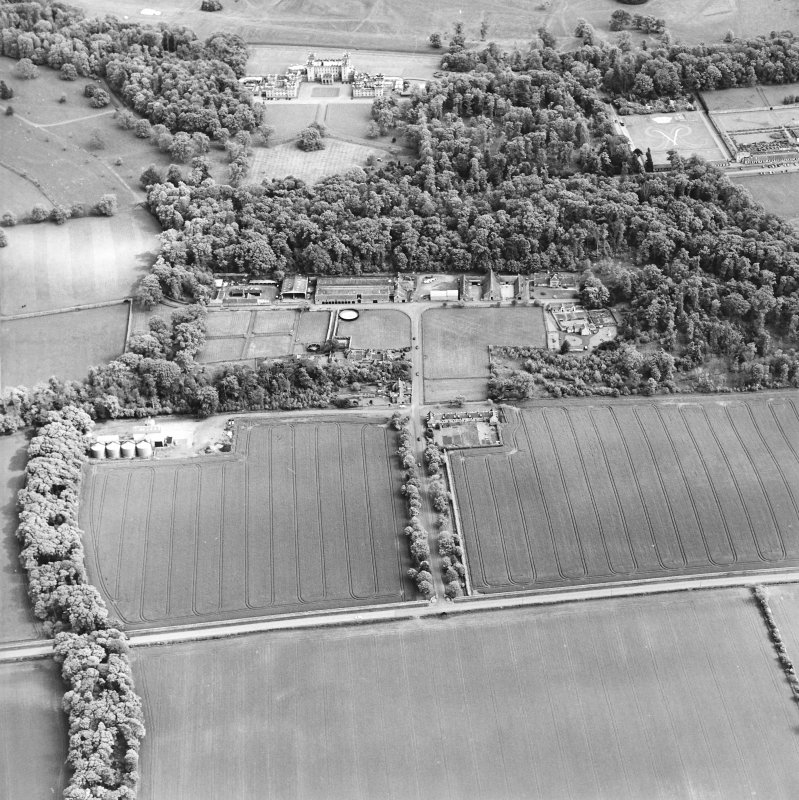 Oblique aerial view centred on the farmsteading, kennels and cottage with country house and formal garden adjacent, taken from the NW