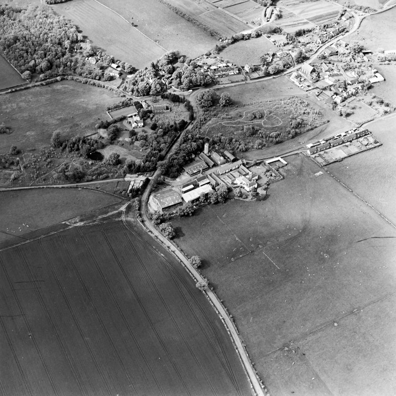 Oblique aerial view centred on the farmsteadings, church and burial ground with village adjacent, taken from the SSE