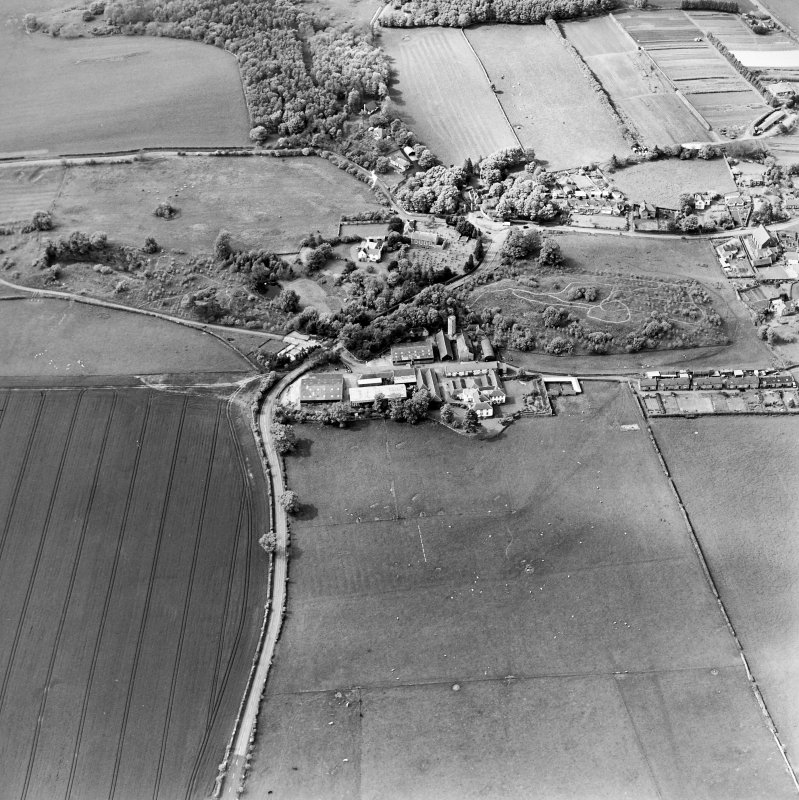 Oblique aerial view centred on the farmsteadings, church and burial ground with village adjacent, taken from the SE