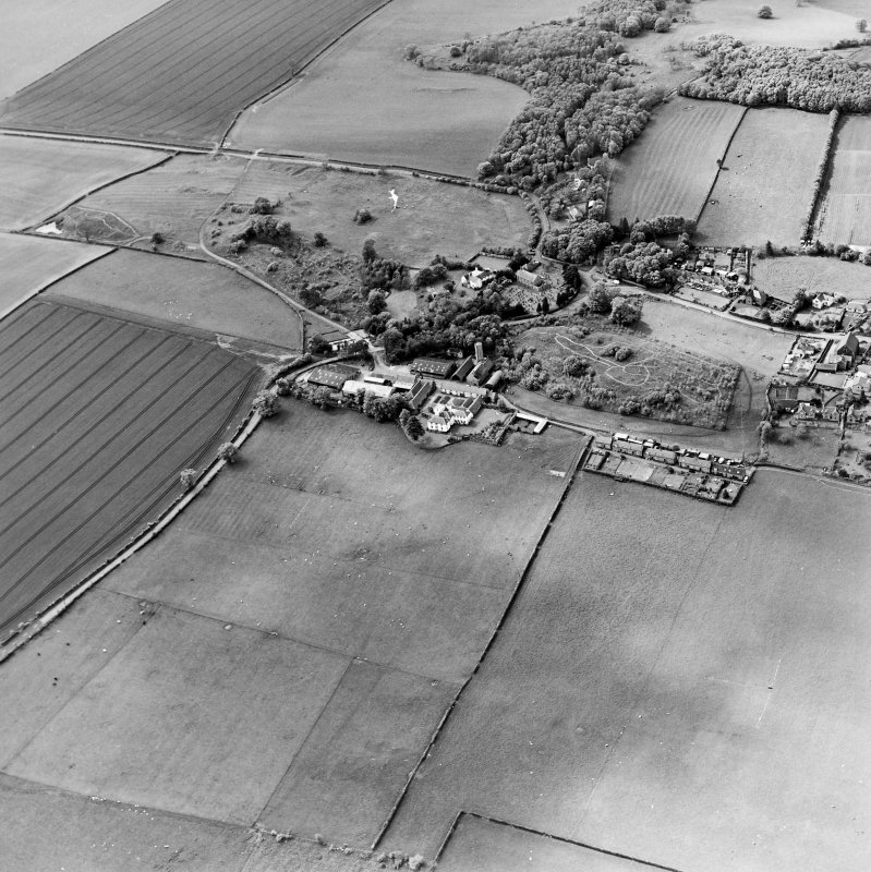 Oblique aerial view centred on the farmsteadings, church and burial ground with village adjacent, taken from the ESE