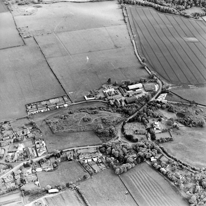 Oblique aerial view centred on the farmsteadings, church and burial ground with village adjacent, taken from the NNW