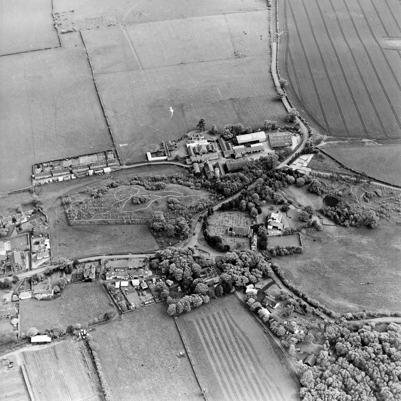 Oblique aerial view centred on the farmsteadings, church and burial ground with village adjacent, taken from the NW