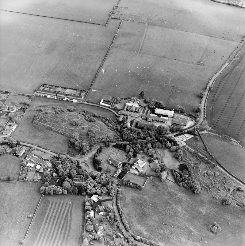 Oblique aerial view centred on the farmsteadings, church and burial ground with village adjacent, taken from the WNW