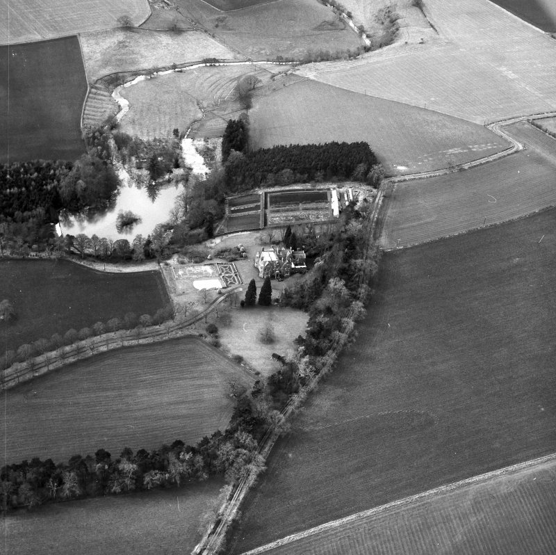 Oblique aerial view centred on country house from E.