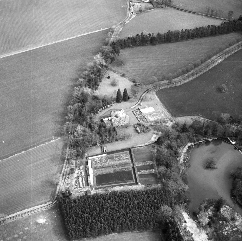 Oblique aerial view centred on country house from W.