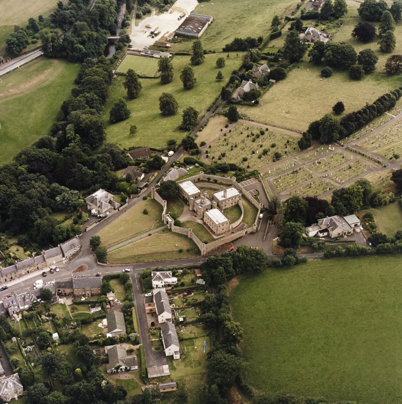 Oblique aerial view centred on the jail, burial ground and The Hermitage, taken from the NW.