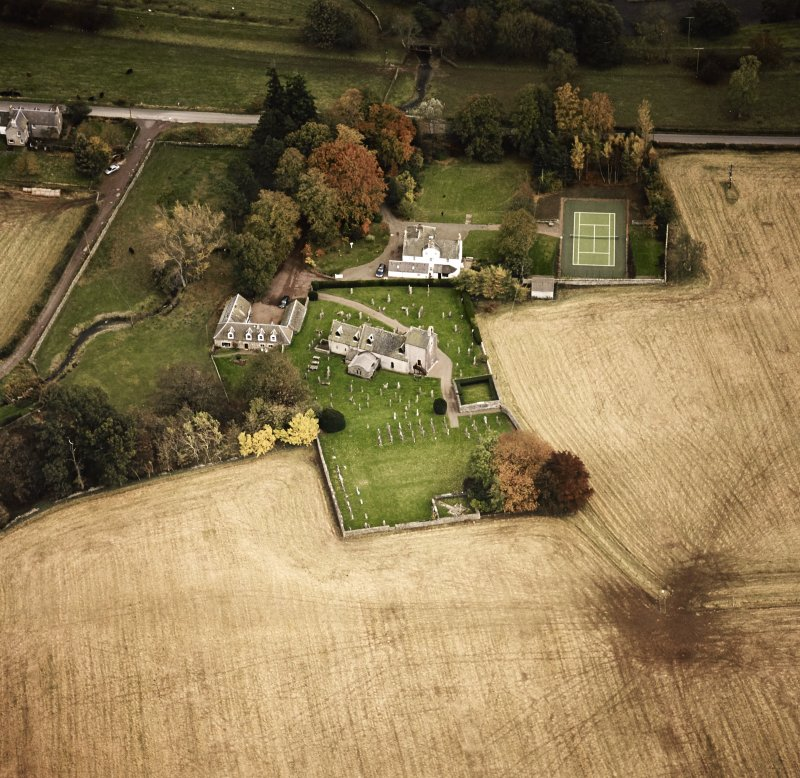 Oblique aerial view centred on the church and manse, taken from the NW.